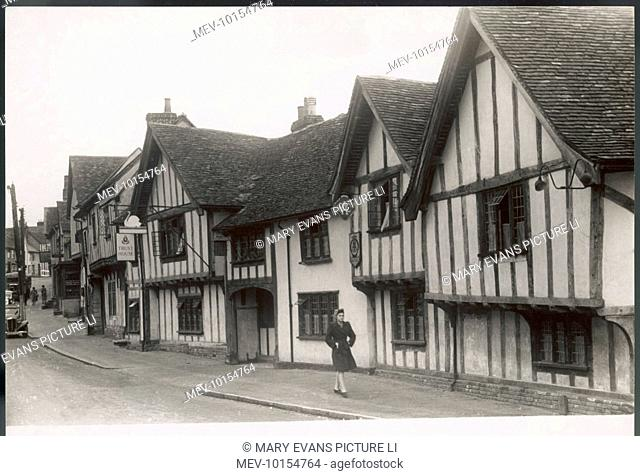 A rather fashionable young woman walks past The Swan, Lavenham, Suffolk, England, a village where Tudor houses, with their wattle walls and lattice windows
