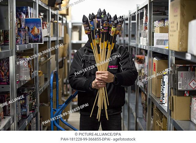 28 December 2018, North Rhine-Westphalia, Eitorf: An employee of Weco, manufacturer of fireworks, holds New Year's Eve rockets in a storage room