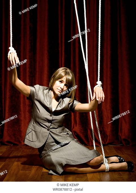 businesswoman being pulled by strings like a puppet