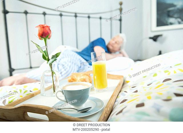 Breakfast tray on bed while mature man in background