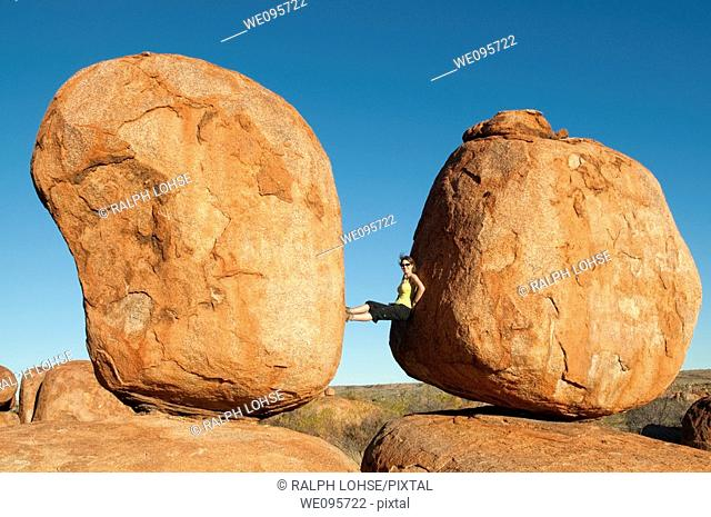Devils Marbles - Woman between two rocks in Devils Marbles Conservation Reserve, Northern Territory, Australia