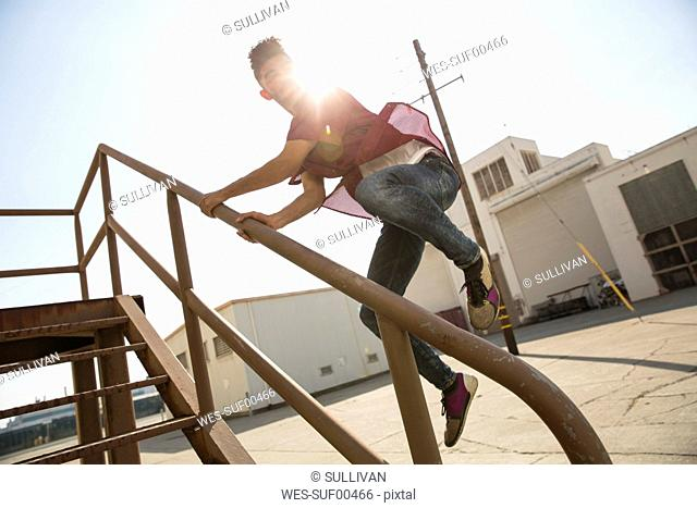 Young man jumping on stairs outdoors