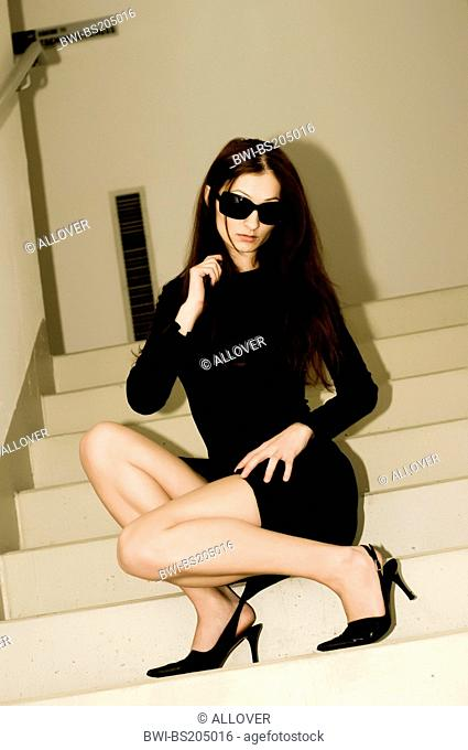 young attractive woman in a black dress, wearing sunglasses, posing on stairs