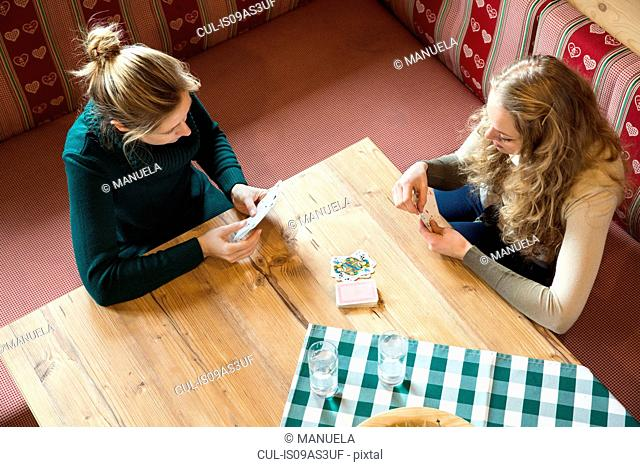 High angle view of two young women playing cards in log cabin