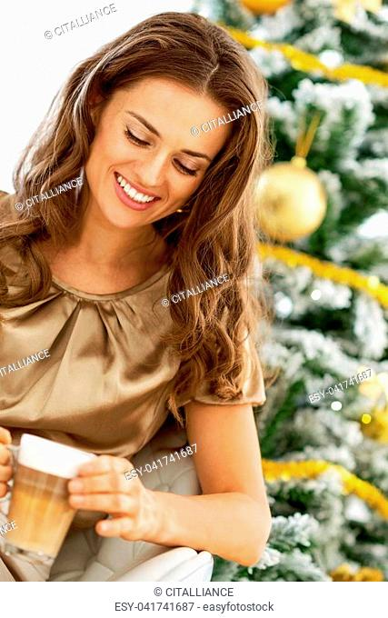 Young woman with latte macchiato in front of christmas tree