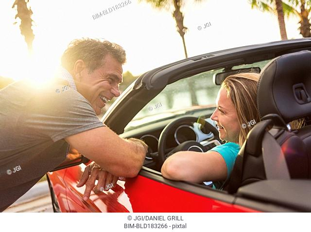 Caucasian couple talking in convertible