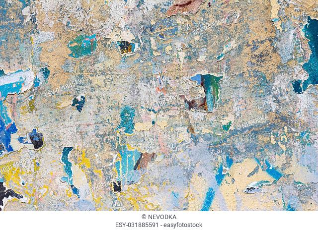 Grunge concrete wall with ripped posters and graffity texture