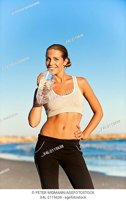 young, pretty, sportive woman on the beach, drinks from water bottle (model-released)