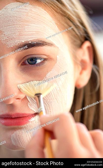 Cosmetologist Applying Facial Mask on Young Woman