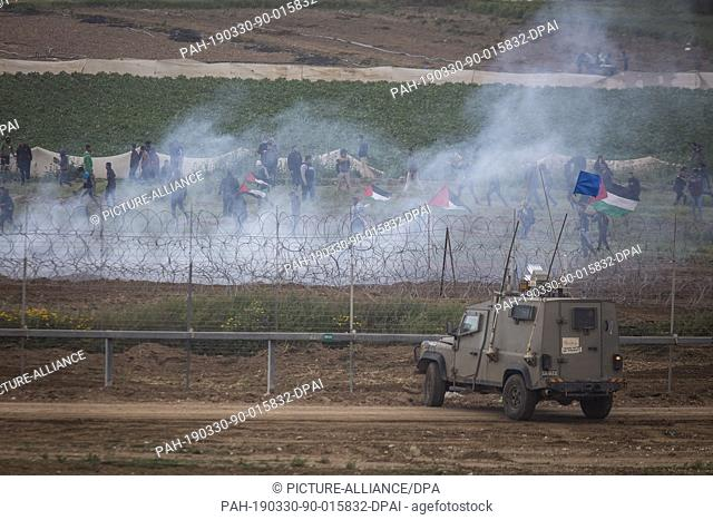 30 March 2019, Israel, Nahal Oz: A picture taken from the Israeli side of the Israel-Gaza border shows the Israeli forces firing tear gas on Palestinian...