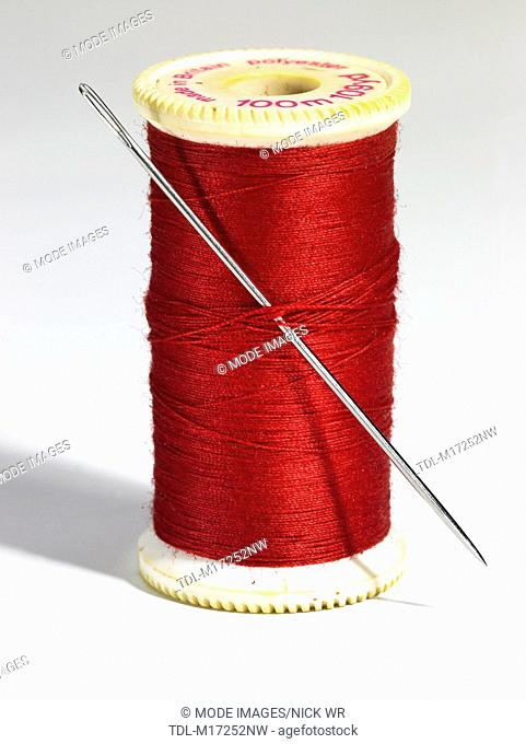 A reel of red cotton thread and a needle