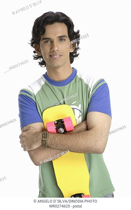 Teenage boy standing with skate board holding in hand to close to body MR 687T