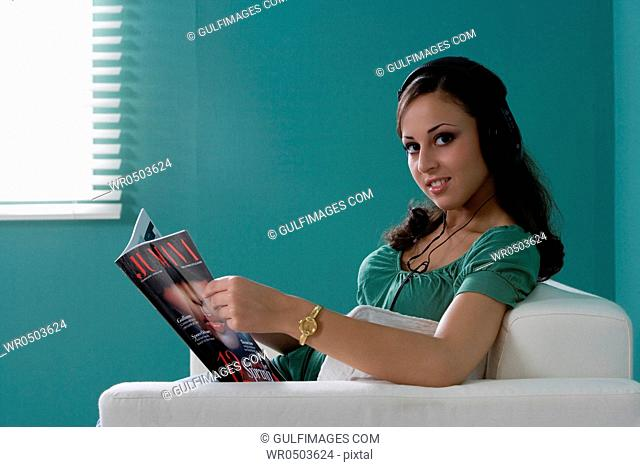 Young woman with headphone reading a magazine