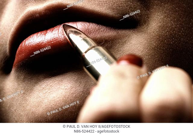 Woman applying lipstick with bullet, conceptual