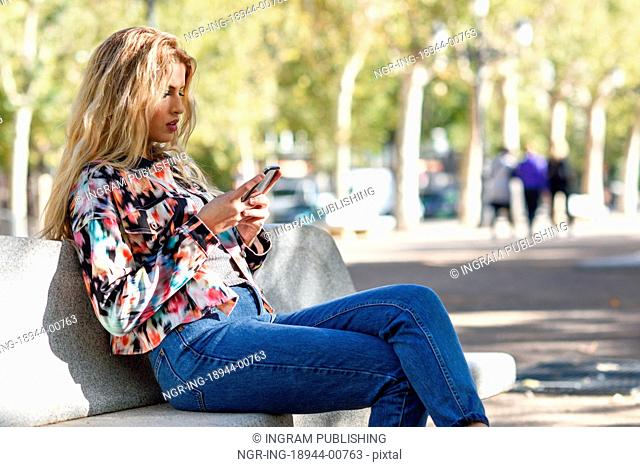 Portrait of blond woman sitting on a bench in the street writting a text message with her smartphone