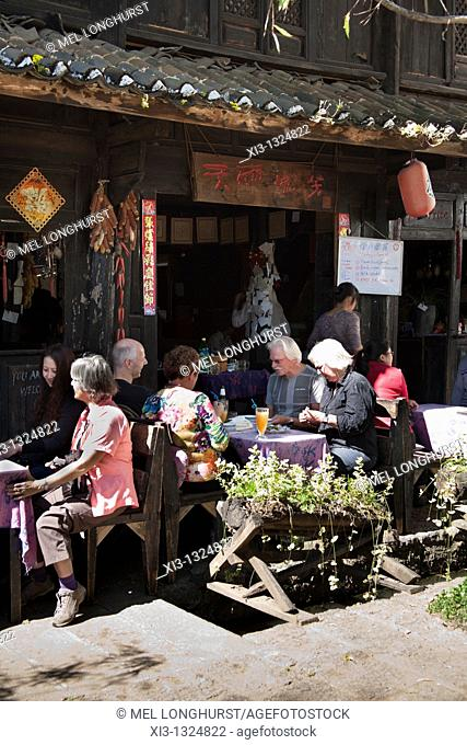 Western tourists dining outside a restaurant, Baisha village, near Lijiang, Yunnan Province, China