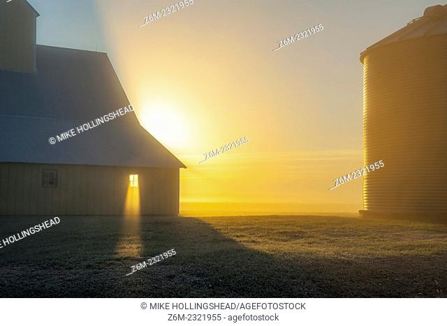 Sun rays shine through barn window on foggy morning in western Iowa