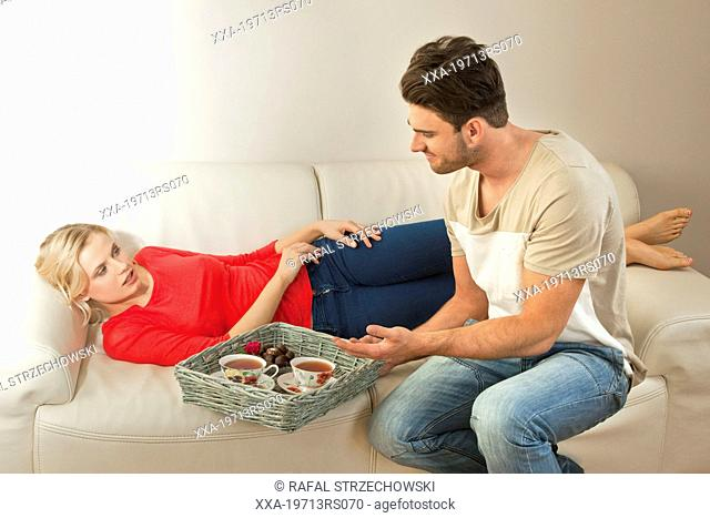 Man serving tea to woman