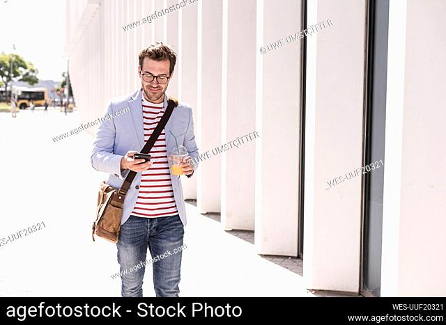 Young man in the city with cell phone and takeaway drink, Lisbon, Portugal