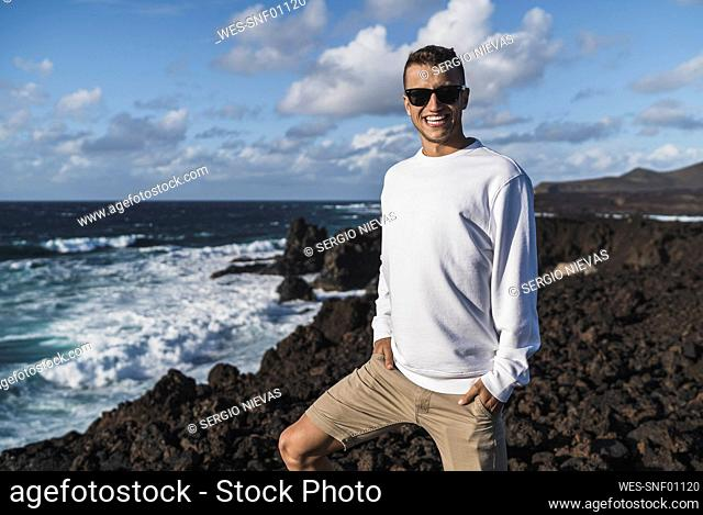 Smiling male tourist with hands in pockets standing on viewpoint by sea at Los Hervideros, Lanzarote, Spain