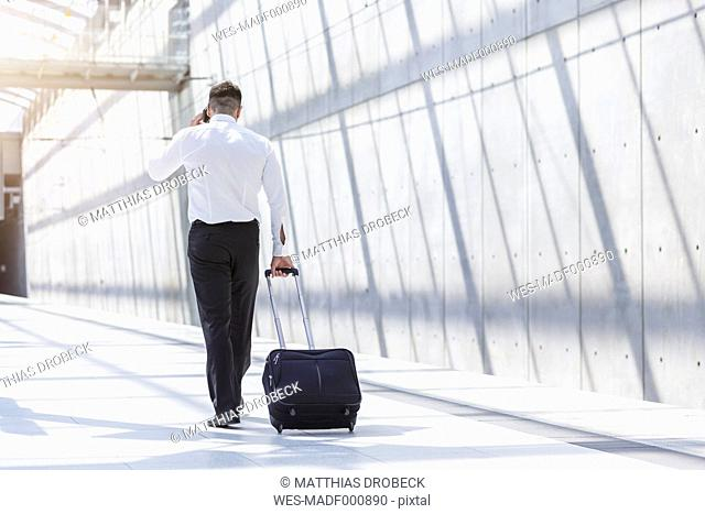 Businessman with luggage and cell phone on the move