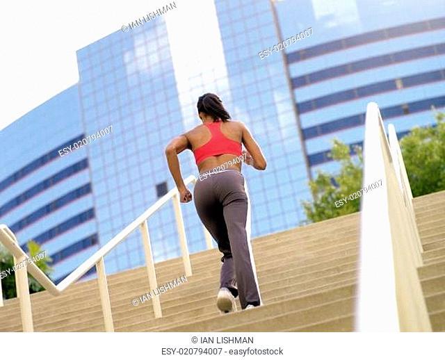 Woman running up stairs, rear view (tilt)