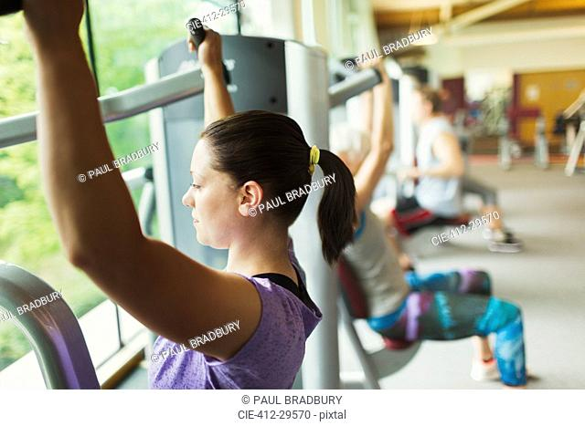 Focused woman using exercise equipment at gym