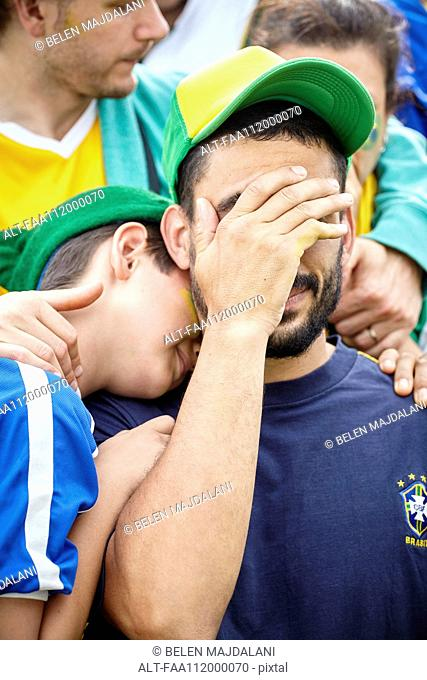 Brazilian football fans looking sad after football match