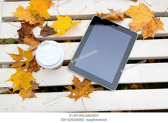 season, technology and advertisement concept - tablet pc computer and coffee paper cup on bench in autumn park