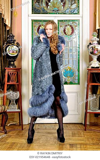 beautiful woman in fur coat in the luxurious antique interior