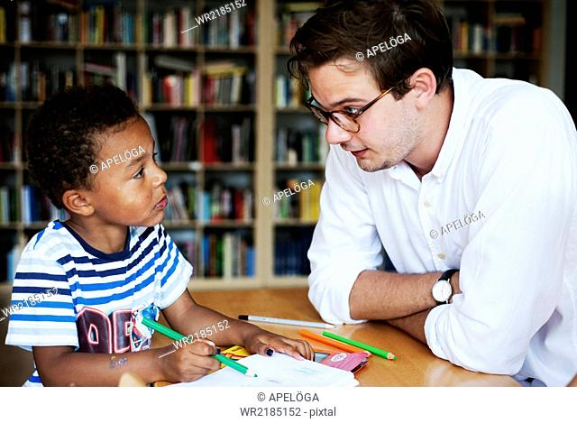 Boy and teacher looking at each other in classroom