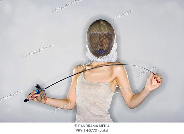 a fashionable woman with a sword in her hand and a helmet on her head