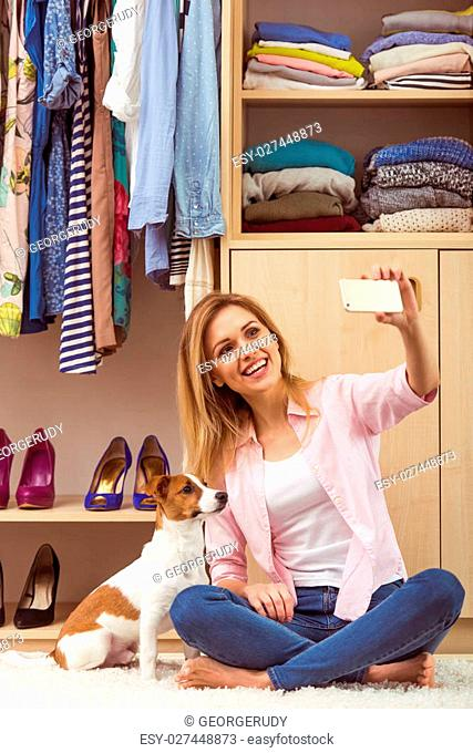 Beautiful girl is smiling and making a selfie with her cute dog, sitting in her dressing room