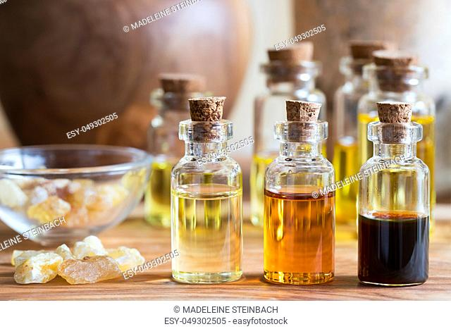 Bottles of essential oil with rankincense resin on a wooden table