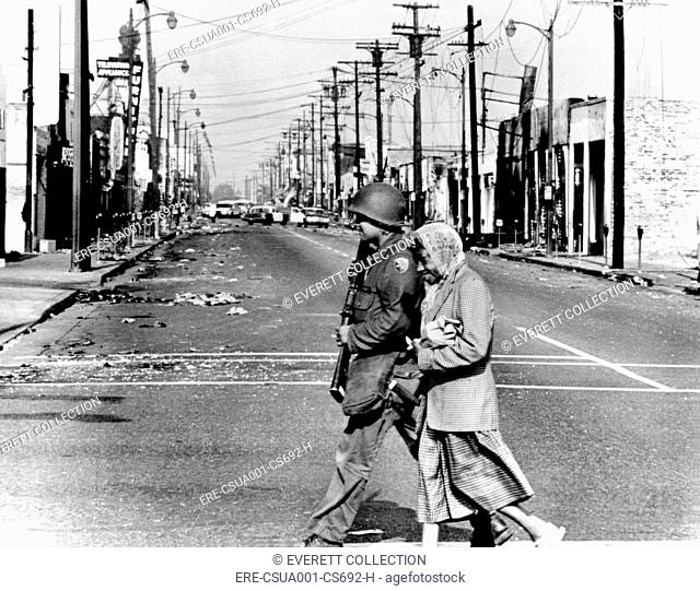 Peace in the midst of Riot. A National Guardsman escorts an elderly African American woman resident of the riot area across fire and violence-scarred street of...