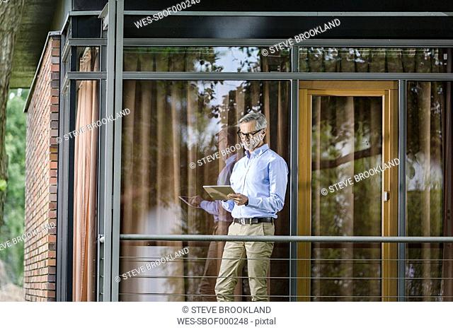 Man standing on balcony of his house looking at tablet