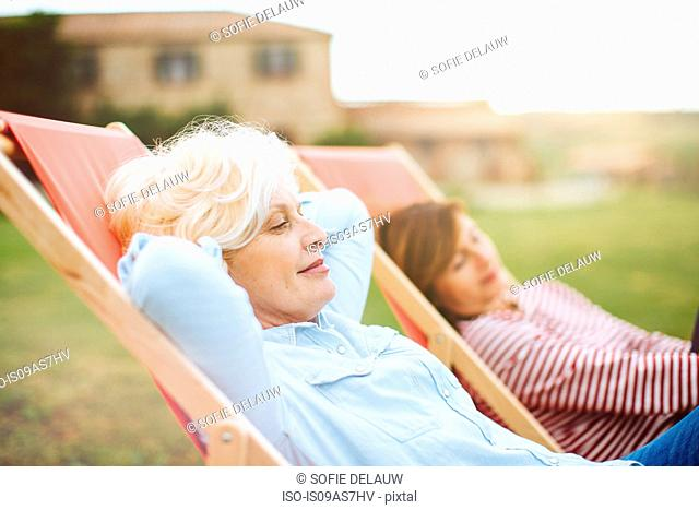 Two mature female friends sitting on deck chairs in front of villa, Tuscany, Italy