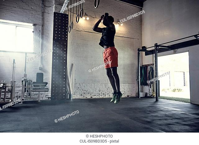 Man in gym jumping in mid air