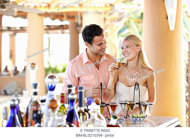 Couple drinking tequila in bar