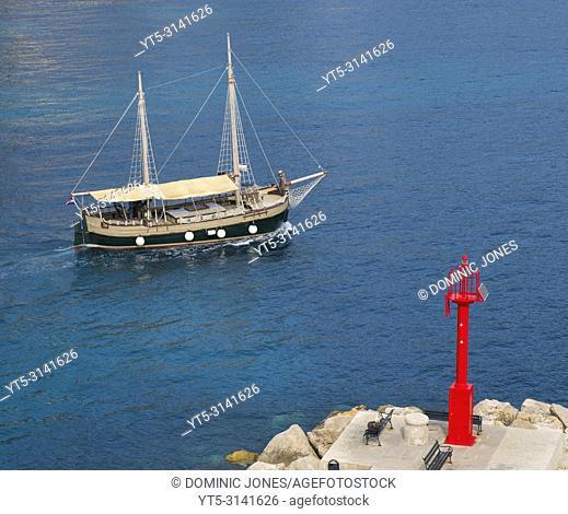 A tour boat sails past the Porporela , Dubrovnik, Croatia, Europe