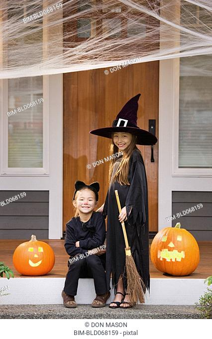 Mixed race young girls in cat and witch costumes