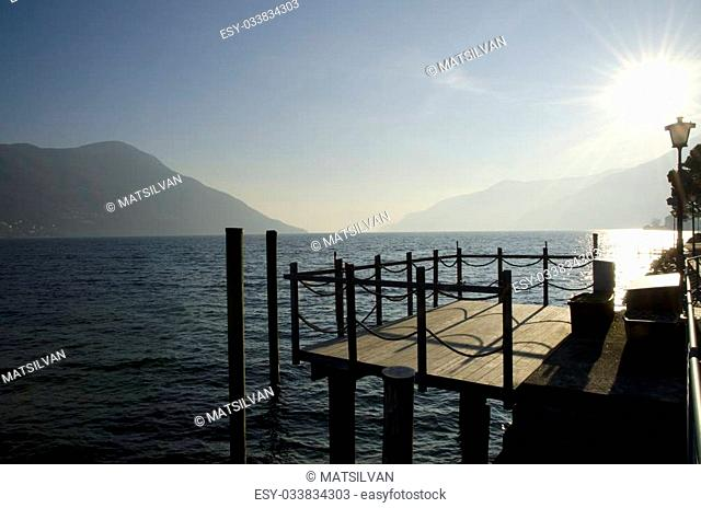 Pier in backlight on a misty alpine lake with mountain and blue sky