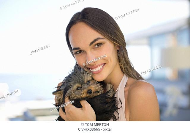 Portrait smiling woman cuddling small dog