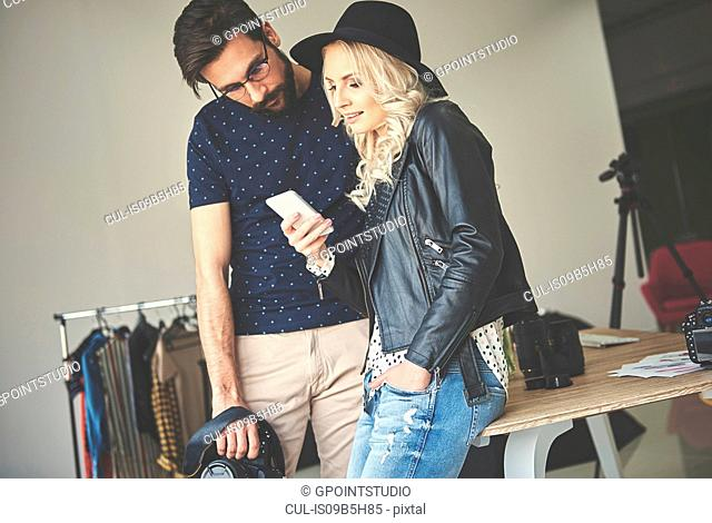 Photographer and stylist looking at smartphone in photography studio