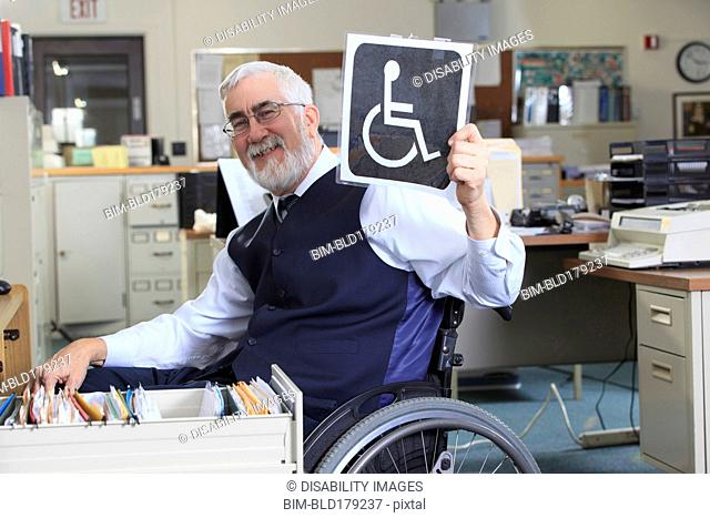 Caucasian businessman holding handicapped sign in office