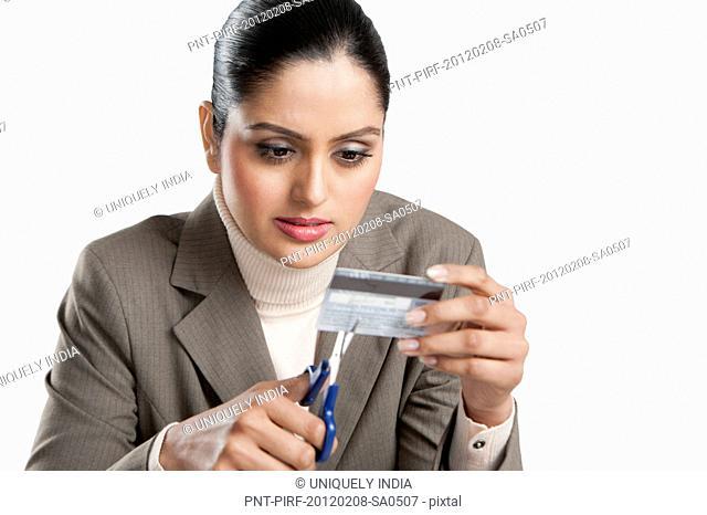 Businesswoman cutting a credit card