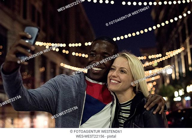 Happy young man with girlfriend taking a selfie at night