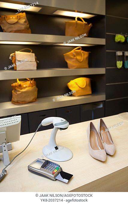 Shoes on clerk desk in retail shop. Card reader, price scanner and bags or shoulder bags. Pricing, scanner, debit machine