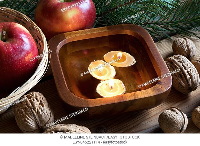 Christmas decoration on a table - apples, pine branches, walnuts and floating candles made from nutshells and beeswax