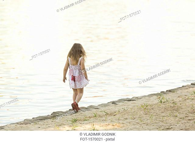 Rear view of girl standing at lakeshore